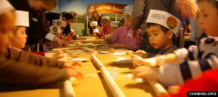 Visitors to the Jewish Children's Museum roll out matzah dough during a pre-Passover workshop.