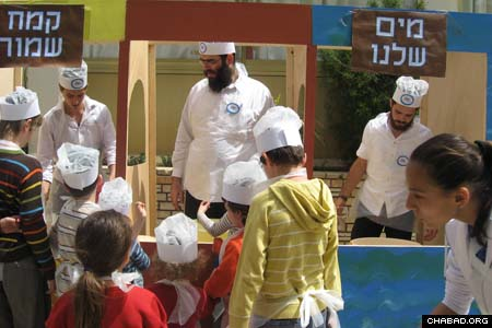 Jewish children in Cyprus line up for a model matzah bakery presided over by Chabad-Lubavitch Rabbi Zeev Raskin. The program traced every step in the genesis of the special hand-made unleavened bread known as shmura matzah, from the milling of the wheat to the dough's super-quick kneading, rolling and baking.