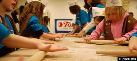 Children from Rochester, N.Y.'s Sinai Hebrew School roll out matzah at a model bakery presented by Chabad-Lubavitch Rabbi Nechemia Vogel.
