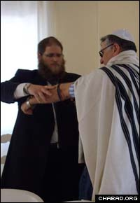 Rabbi Chaim Hillel Azimov helps a Jewish resident of Northern Cyprus don tefillin.