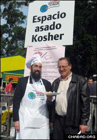 Rabbi Eliezer Shemtov, left, co-director of Chabad-Lubavitch of Uruguay, stands with Montevideo Mayor Ricardo Ehrlich at the kosher booth of the world's largest barbeque.