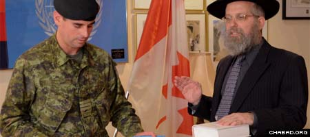 Chabad-Lubavitch Rabbi Lazer Danzinger, right, takes the oath of office administered by Lt. Col. Andrew Zalvin, commanding officer of the 32nd Canadian Brigade.