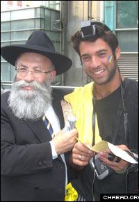 Rabbi Yaakov Gloiberman, left, helps a fan of the Maccabi Tel Aviv basketball team put on tefillin.