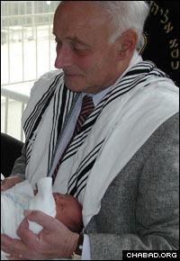 Liviu Librescu serves as the sandak for his grandson's circumcision in Israel.