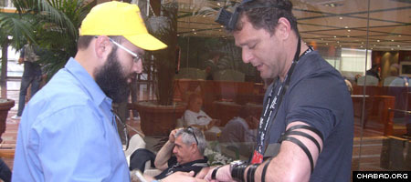 A fan of the Maccabi Tel Aviv basketball team dons tefillin just before a Euroleague Final Four game in Madrid.