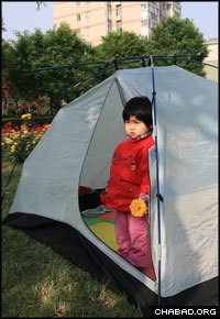 A little girl looks out from her tent in downtown Chengdu, China, after a powerful 7.9 magnitude earthquake prompted residents of the city's towers to move to the streets outside. (Photo: Bruce Lee)