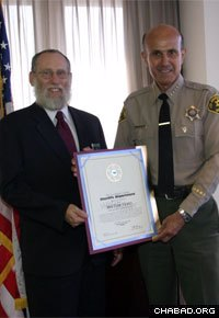 Rabbi Bentzion Kravitz, a volunteer police chaplain, receives an award from the Los Angeles Sheriff's Department.