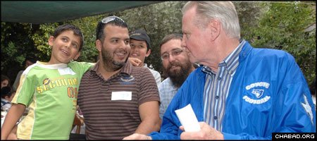 Academy Award winner Jon Voight, right, gives words of encouragement to wounded Israeli border policeman Aharon Gozlan in a meeting arranged by Chabad's Terror Victims Project. (Photo: Meir Dahan)