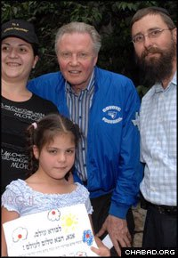 """Rabbi Menachem Kutner, right, of Chabad's Terror Victims Project accompanies American actor Jon Voight on a visit with Jerusalem's Hondiashvili family. The little girl, whose father Baruch Hondiashvili was killed in the Jan. 29, 2004 suicide bombing of Jerusalem's Bus No. 19, holds a letter to G-d that says: """"Creator of the world, please bring peace to the world."""" (Photo: Meir Dahan)"""