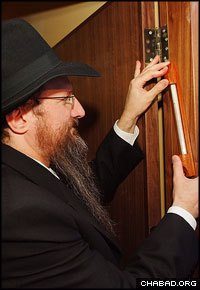 Chabad-Lubavitch Rabbi Berel Lazar, chief rabbi of Russia, affixes a mezuzah to the new Kiryat Hasofrim, an interactive museum and scribal arts factory in Safed, Israel.