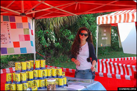 """The """"Bringing Meron to Miami"""" Lag B'Omer party and festival began in daylight with a series of booths exploring different mitzvahs. Here, a volunteer puts the finishing touches on an exhibit dedicated to tzedakah, or the giving of charity. Visitors to the booth walked away with their very own tzedakah boxes."""
