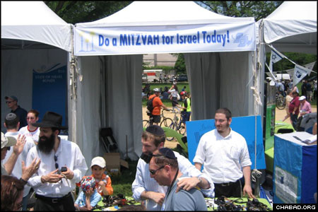 "Rabbi Sholom Raichik, director of Chabad-Lubavitch of Upper Montgomery County in Maryland, coordinated the ""Do a Mitzvah for Israel"" booth at Sunday's Israel @ 60 celebration held at the National Mall in Washington, D.C. More than 1,000 people stopped by to don tefillin, pick up Shabbat candles, or drop a coin in the charity box. American Friends of Lubavitch helped arrange the presence at the Jewish Federation of Greater Washington event."