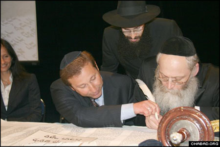 Alexander Bachrach, sponsor of Smolensk, Russia's new Torah, fills in one of the holy scroll's letters with the help of ritual scribe Rabbi Moshe Klein of New York.