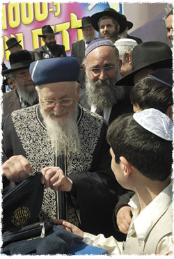 Le Rav Eliyahou à une cérémonie organisée par Colel 'Habad lors de laquelle il donna à 500 garçons bar-mitsva une paire de Téfiline, parlant ici avec l'un des bar-mitsvas de l'importance de cette mitsva