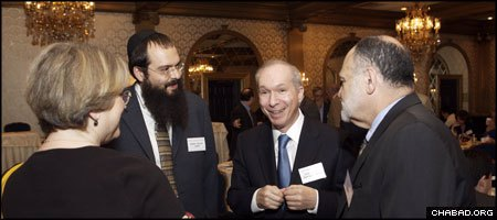 Chabad-Lubavitch Rabbi Shalom Lubin, second from left, and New Jersey Supreme Court Justice Barry T. Albin, talk with attendees at the second-annual Jewish Law Symposium.