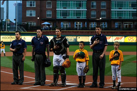 Officials and little league players stand for the National Anthem before the July 23 Jewish Pride Night at Manchester, N.H.'s Merchantsauto.com stadium. After the game, the hometown minor league New Hampshire Fisher Cats fell to the Trenton Thunder, 3-1.