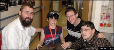 Rabbi Menachem Kutner, left, visited nine-year-old Osher Tuito with Yudi Zeller and Zelig Bergman, two Americans who delivered a laptop computer to the Israeli terror victim.