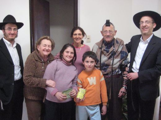 A family of Mitzvot. As you can see, grandpa is wearing Tefillin, his granddaughter is holding a new set of candles for Shabbat, and her brother is holding a charity box.