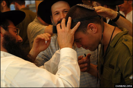 The idea for the bar mitzvah came to Ron, right, when a young Chabad-Lubavitch rabbinical student visited his base. The student, who regularly helped soldiers put on tefillin, learned that Ron had never before donned the prayer boxes worn by Jewish men the world over, and half-jokingly suggested that the officer celebrate his bar mitzvah on the spot. Ron, however, wanted a big party.