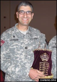 U.S. Army Capt. Henry Soussan holds a Torah scroll sent to his base in Kuwait by the Florida-based Aleph Institute.