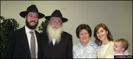 Rabbi Moshe Katsenelenbogen, second from left, rescued a Torah scroll from a synagogue destroyed by Soviet authorities decades ago. Standing with him are his wife Zelda, and his son and daughter-in-law, Rabbi Nochum and Chanie Katsenelenbogen.
