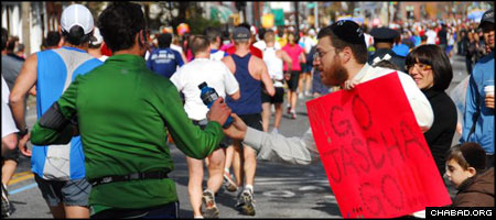 Rabbi Zev Wineberg, co-director of Chabad-Lubavitch of Long Island City, passes out bottles of kosher sports drink to runners in Sunday's New York City Marathon. (Photo: Yosef Lewis)