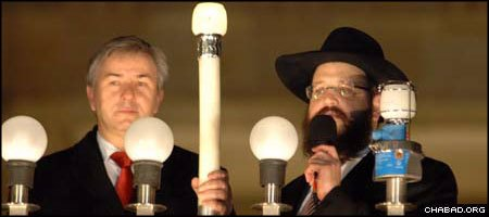 Berlin Mayor Klaus Wowereit, left, joins Rabbi Yehuda Tiechtel, co-director of Chabad-Lubavitch of Berlin, in lighting the Chanukah menorah in front of the Brandenburg Gate last year.