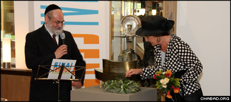 Joined by Chabad-Lubavitch Rabbi Binyomin Jacobs, Princess Margriet of the Netherlands lights a candle in the synagogue at the newest branch of the Sinai Centrum Psychiatric Hospital.