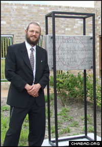 Rabbi Daniel van Praag, head chaplain at the Sinai Center, stands next to a memorial to a Dutch hospital's 1,200 psychiatric patients and their caregivers who were murdered by Nazi forces during World War II.
