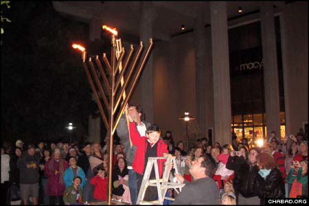 A child assists in the lighting of the Unity Menorah erected outside an area mall by Chabad-Lubavitch of S. Barbara. Mayor Marty Blum also assisted in the ceremony, as did community member Seth Olitzky, who lost his home in the fires that swept through Southern California last fall.