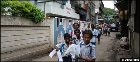 Reclaiming the past: Children run outside the Chabad House in Mumbai months before its destruction in the November terror attacks. Chabad-Lubavitch officials saw in a public menorah lighting that took place on Thursday the return of light to the center.