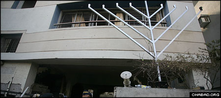 A Chanukah menorah stands at the entrance to the destroyed Chabad House in Mumbai one month after the terror attacks that claimed the lives of its directors, Rabbi Gavriel and Rivka Holtzberg. (Photo: Meir Alfasi)