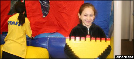 A child holds a Chanukah menorah made out of Lego pieces earlier this week at the Chanukah Wonderland operated by Chabad-Lubavitch of the Five Towns.
