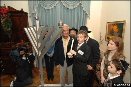 Ari Oirechman, 8, lights the Chanukah menorah at the Florida state capitol in Tallahassee as his mother Chanie Oirechman, co-director of Chabad-Lubavitch of Tallahassee, looks on.