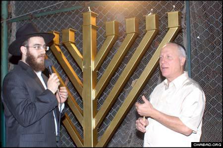 Local businessman Asher Saddan kindles the Chanukah menorah.