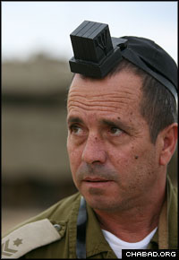 An Israeli soldier dons tefillin during a visit by Chabad-Lubavitch emissaries to his base near the Gaza Strip. (Photo: Meir Alfasi)