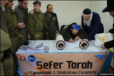 Assisted by a ritual scribe, officers stationed at an army base in Beit El, Israel, fill in the last letters of a Torah scroll donated to the Israel Defense Force by Florida newlyweds Israel and Gabriela Kopel. (Photos: Berel Sheiner)