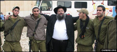 Chabad-Lubavitch Rabbi Moshe Ze'ev Pizem dances with Israeli soldiers headed to the Gaza front at a bus depot.