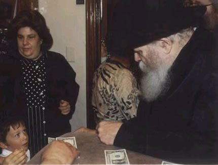Four year old Amo receiving a dollar from the Lubavitcher Rebbe, Rabbi Menachem Mendel Schneerson, of righteous memory.