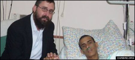 Rabbi Menachem Kutner of Chabad's Terror Victims Project visits with an injured Israeli soldier at Beilinson Hospital in Petach Tikva.