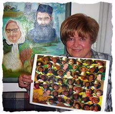 """Batya with a photo of her """"children,"""" and a painting of her parents in the background."""