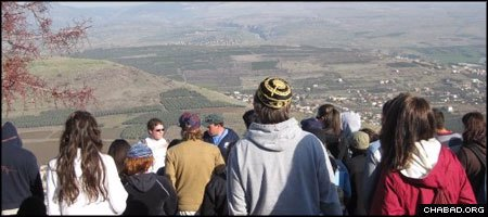 Jewish young adults on a free tour of the Holy Land look out over a valley from Israel's Golan Heights.