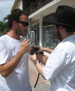 Rabbi Druk helps a tourist put on Tefillin