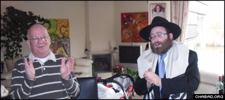 Joined by Rabbi Moshe Stiefel, right, Gavriel Noach van Loon celebrates being ritually circumcised at the age of 63.