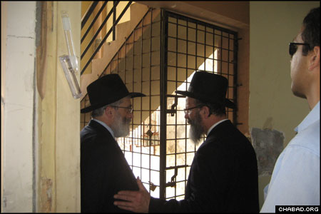 """Philanthropist Rabbi Joseph Gutnick, left, who pledged to help rebuild Chabad of Mumbai """"to be even grander than before,"""" shares a word with Rabbi Nachman Holtzberg, father of murdered Rabbi Gavriel Holtzberg, on a landing at the heavily-damaged site of the former Chabad House."""