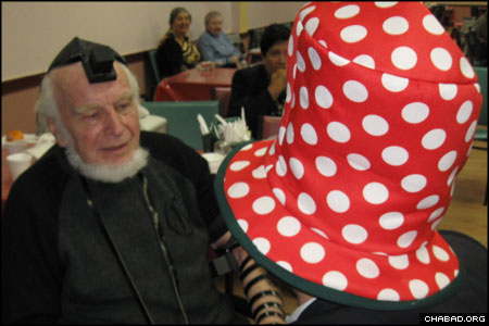 "Wearing an oversized hat in honor of Purim, a Chabad-Lubavitch rabbinical student assists 81-year-old Arnold Edward in donning tefillin for the first time. ""We danced and sang,"" related Tenenbaum. ""90-year-old men were crying."""