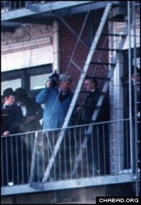 A television crew films the 1981 gathering from a fire escape.