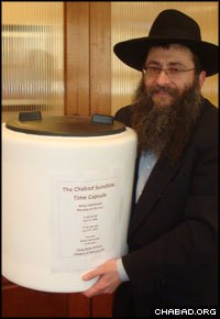 Rabbi Anchele Perl holds the Chabad Sunshine Time Capsule.