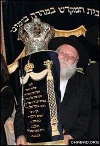 Rabbi Shimon Rosenberg, father of slain Chabad-Lubavitch emissary Rivka Holtzberg, holds a Torah scroll dedicated in her memory.