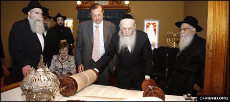 New York-based ritual scribe Rabbi Moshe Klein prepares a new Torah scroll at a dedication ceremony in Toms River, N.J., as members of the extended Popack families look on. Rabbi Shmuel Isaac Popack, right, celebrated his 90th birthday at the ceremony. He was joined by his sons, Rabbi Yisroel Meir Popack, left, and Yosef Yitzchak Popack; his wife, Miriam Popack; and, standing behind, his sons-in-law, Rabbis Yisroel Yosef Hendel and Yitzchak Raskin.